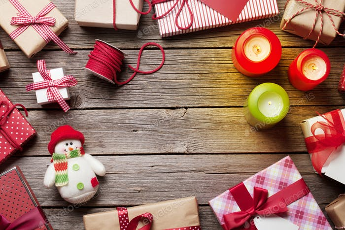 Christmas gift boxes and candles on wooden table