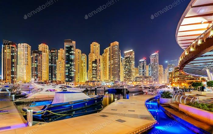 Incredible night dubai marina skyline. Luxury yacht dock. Dubai, United Arab Emirates.