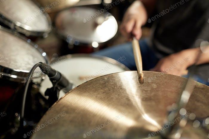 männlicher Musiker spielt Schlagzeug und Becken beim Konzert