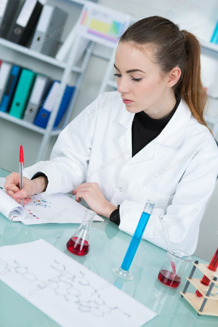 female chemistry student with glassware test flask