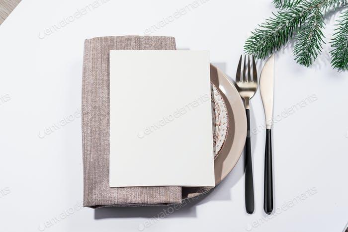 Winter festive table setting with cutlery and white brochure on table. Christmas tableware.