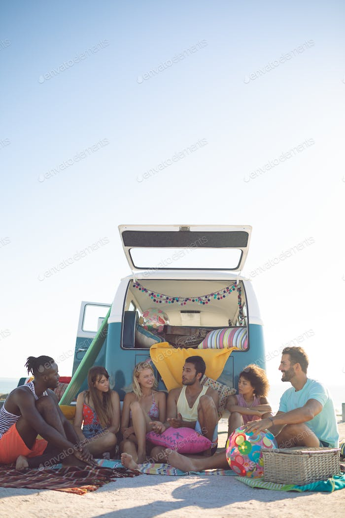 Front view of group of diverse friends interacting with each other near camper van at beach
