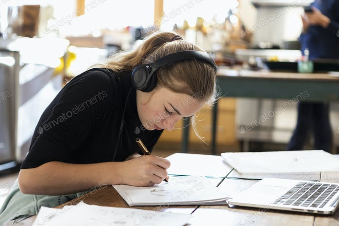 teenage girl wearing headphones, drawing on paper