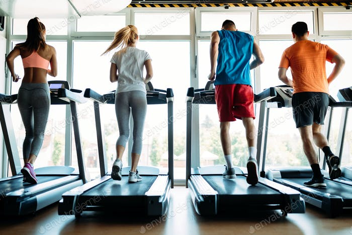 Happy people on treadmills in the gym