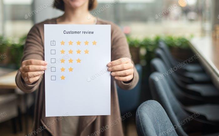 Verschwommenes weibliches Papierbogen mit Fünf-Sterne-Bewertung