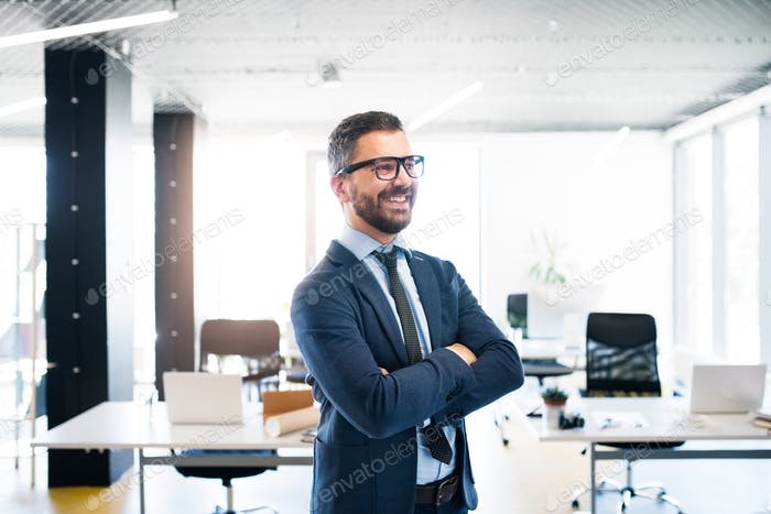 Young hipster businessman with tie and eyeglasses in the office.
