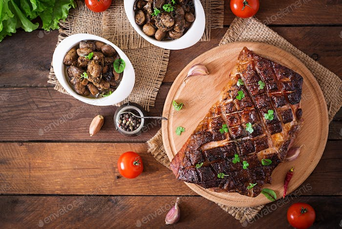 Baked meat with spices and garlic on wooden table. Top view