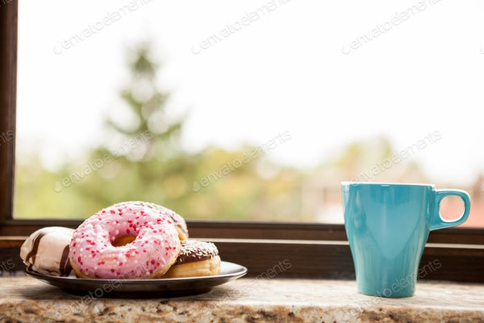 Donuts and a cup of coffee next tot the window sill