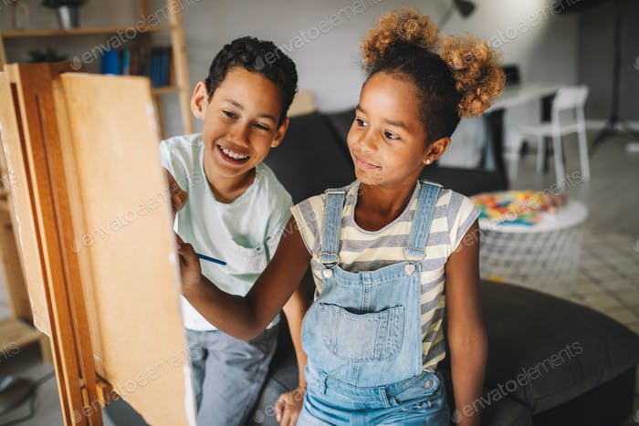 Cute children girl and boy painting together. Education, art, fun and creativity concept