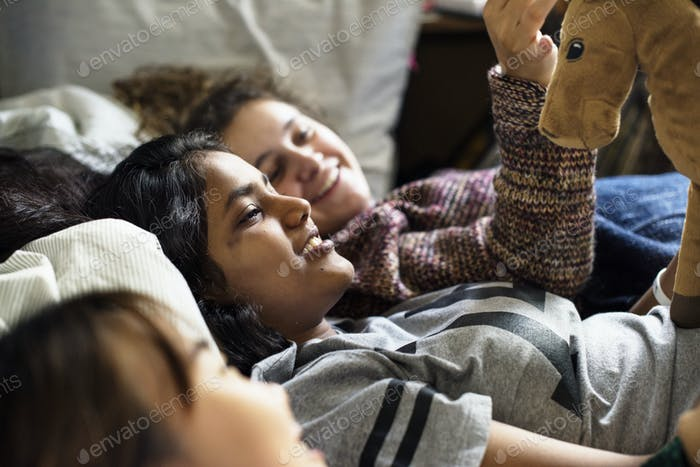 Teenage girls using smartphones on a bed internet in slumber party
