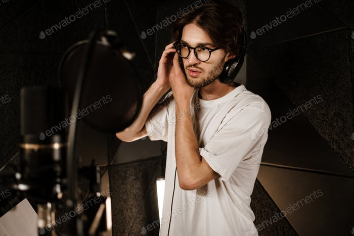 Young male singer wearing headphones preparing recording new song in sound studio