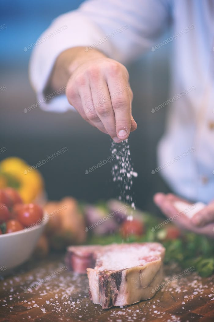 Chef putting salt on juicy slice of raw steak