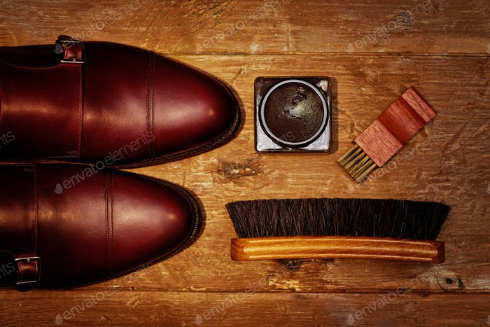 Still life with men's leather shoes and accessories for shoes care.