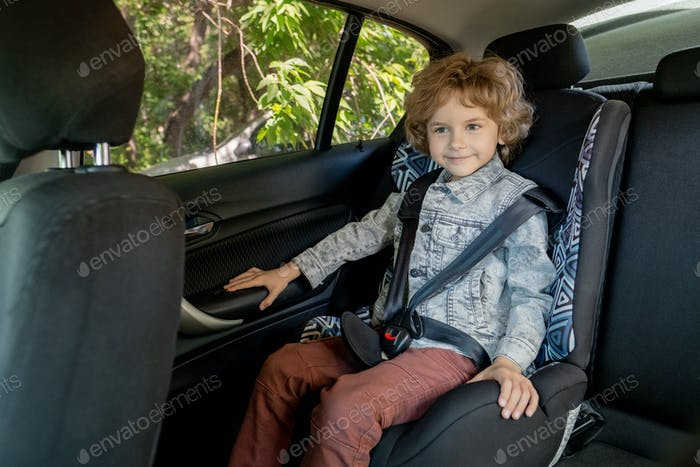 Happy cute boy of elementary age in denim jacket and brown pants sitting in car