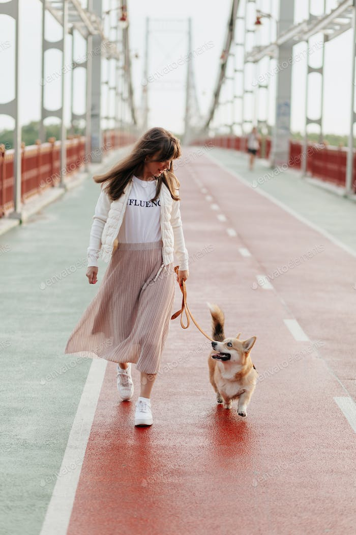 Happy stylish woman walking with her corgi in sunlight on the morning walking