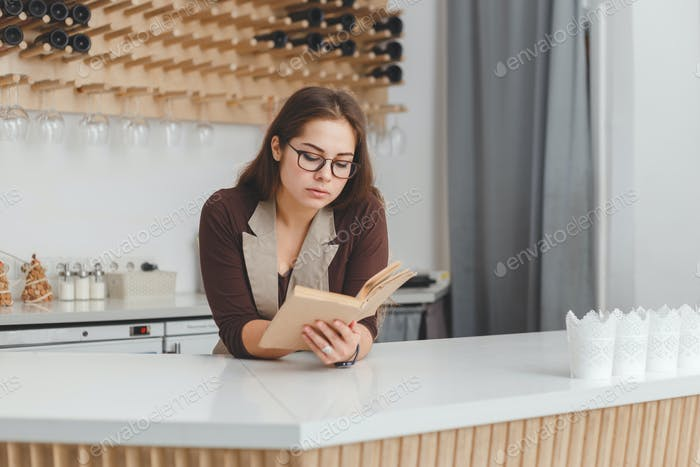 Woman readi ng a recipe on book in modern kitchen