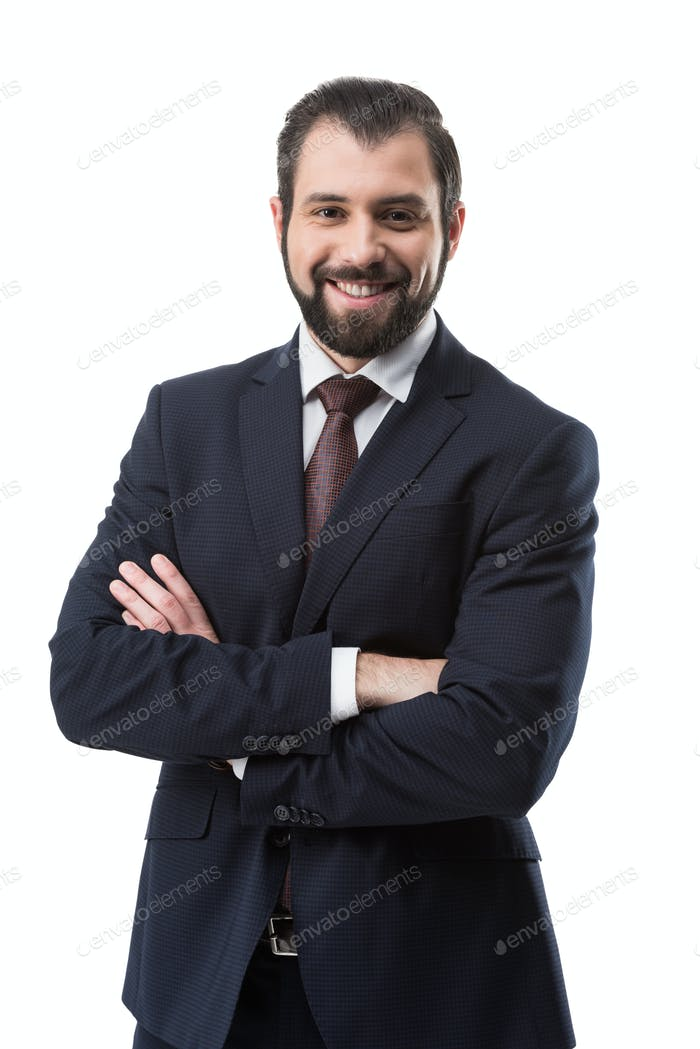 cheerful bearded businessman in suit with crossed arms, isolated on white