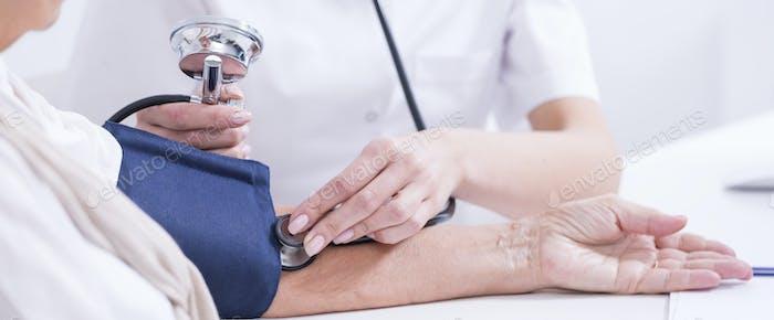 Doctor measuring patient's blood presure