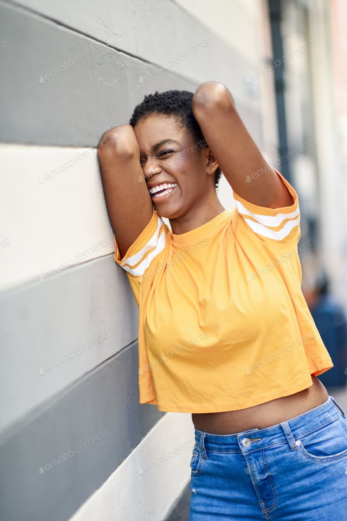 Happy black woman laughing on urban wall