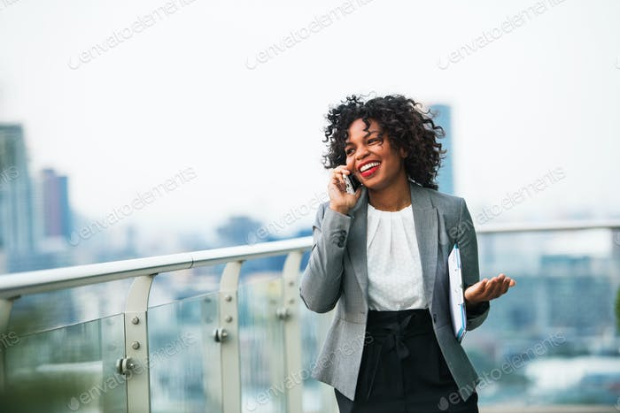 A portrait of a businesswoman standing on a terrace, making a phone call.