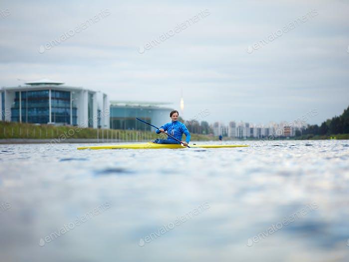 Young Caucasian man in swimming sportswear paddling
