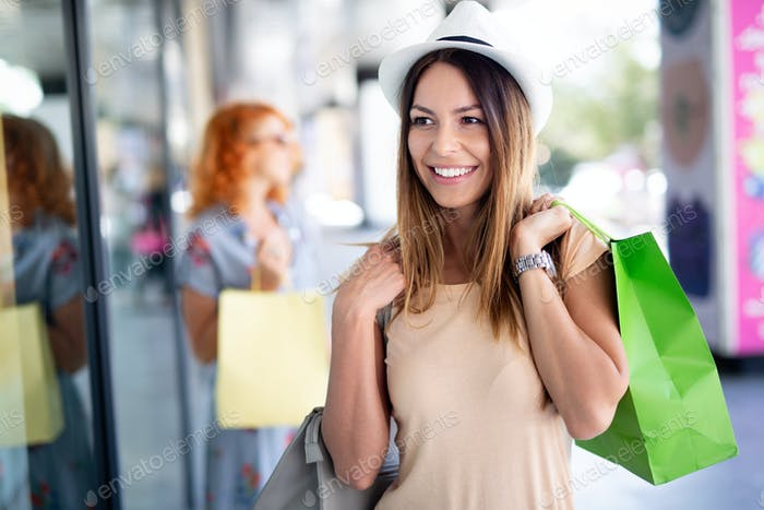 Beautiful smiling young woman with bag in shopping mall