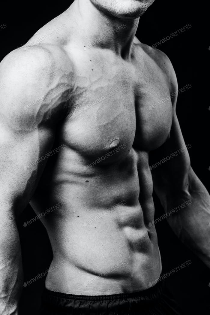 Muscular sexy torso of young sporty man with perfect abs close up. Black and white isolated on black