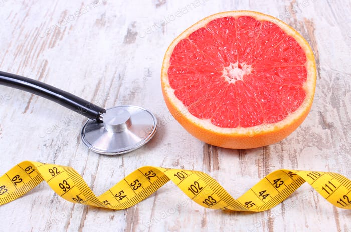 Fresh grapefruit, centimeter and stethoscope on old wooden background
