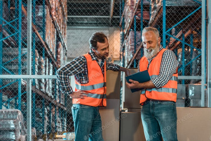 warehouse workers taking notes in clipboard while working together in storehouse