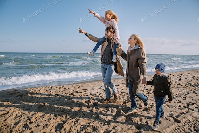 happy family pointing somewhere while walking together on seashore in autumn
