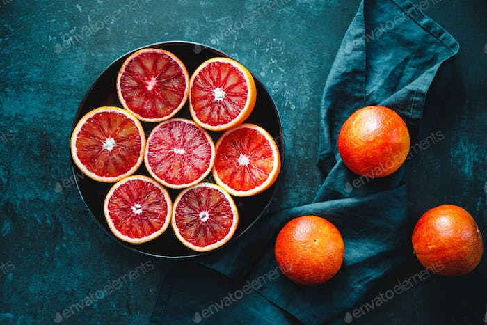 Cutted blood oranges in a plate on a dark blue background.