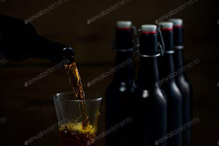 Biergläser und Bierflaschen auf einem hölzernen Hintergrund
