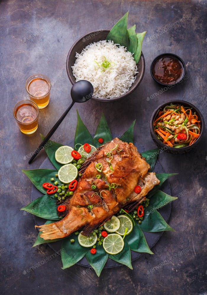 Thai cuisine deep fried fish with salad and rice, top view