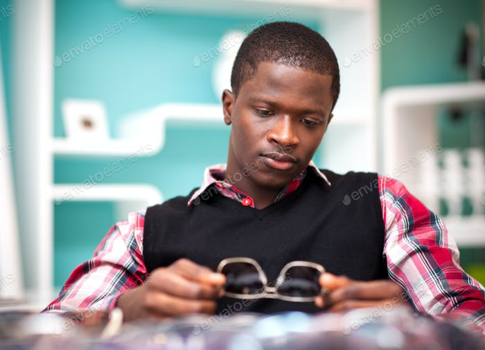 Young handsome african man in stylish casual clothing sitting and looking at sunglasses