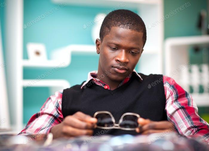 Hombre africano joven guapo en ropa casual con estilo sentado y mirando gafas de sol