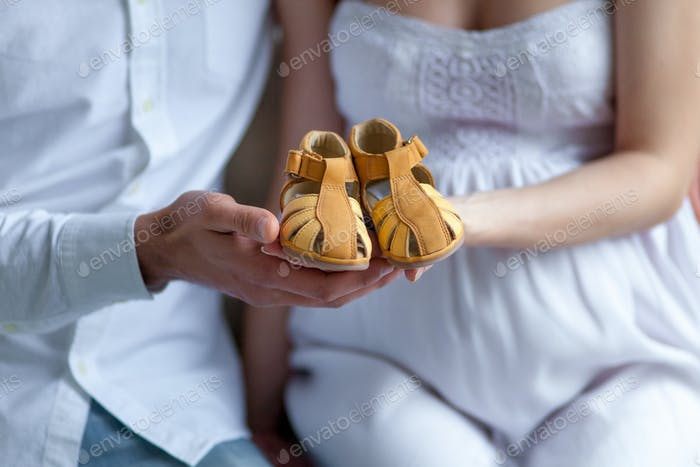 Cheerful young couple with baby shoes sitting at home