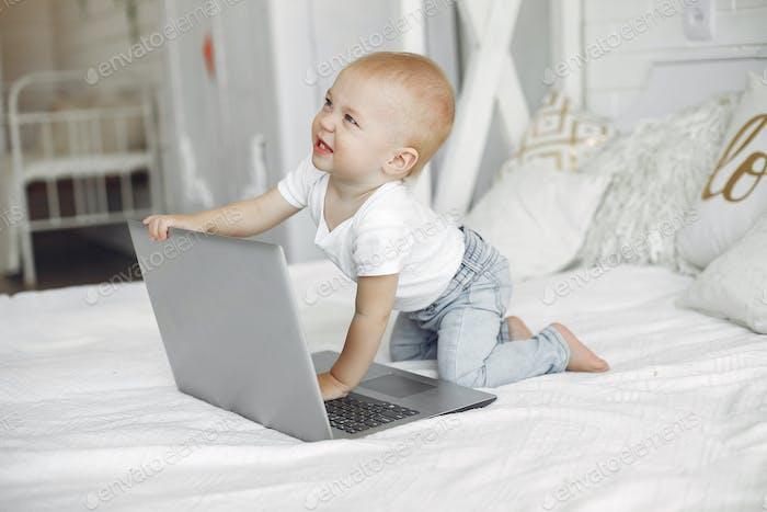 Niedlicher kleiner Junge spielt mit einem Laptop auf einem Bett
