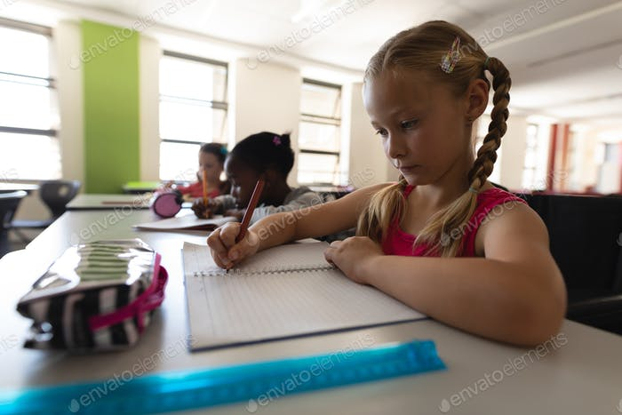 Side view of schoolgirl studying at desk in classroom of elementary school