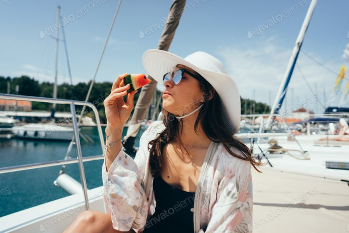 Woman sits on the deck and eats a watermelon