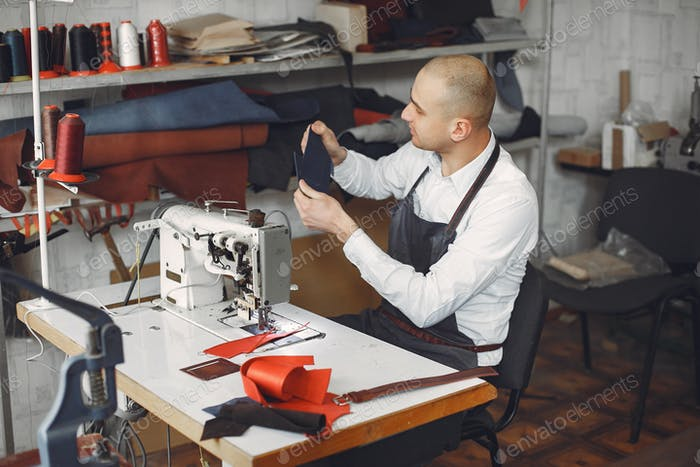 Man in a studio creates leather ware