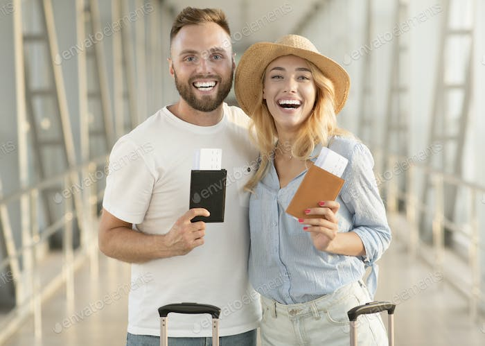 Happy couple with passports and tickets at airport terminal