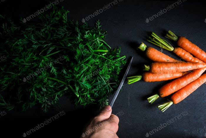 Sliced tops of carrots, carrots and and a knife in hand