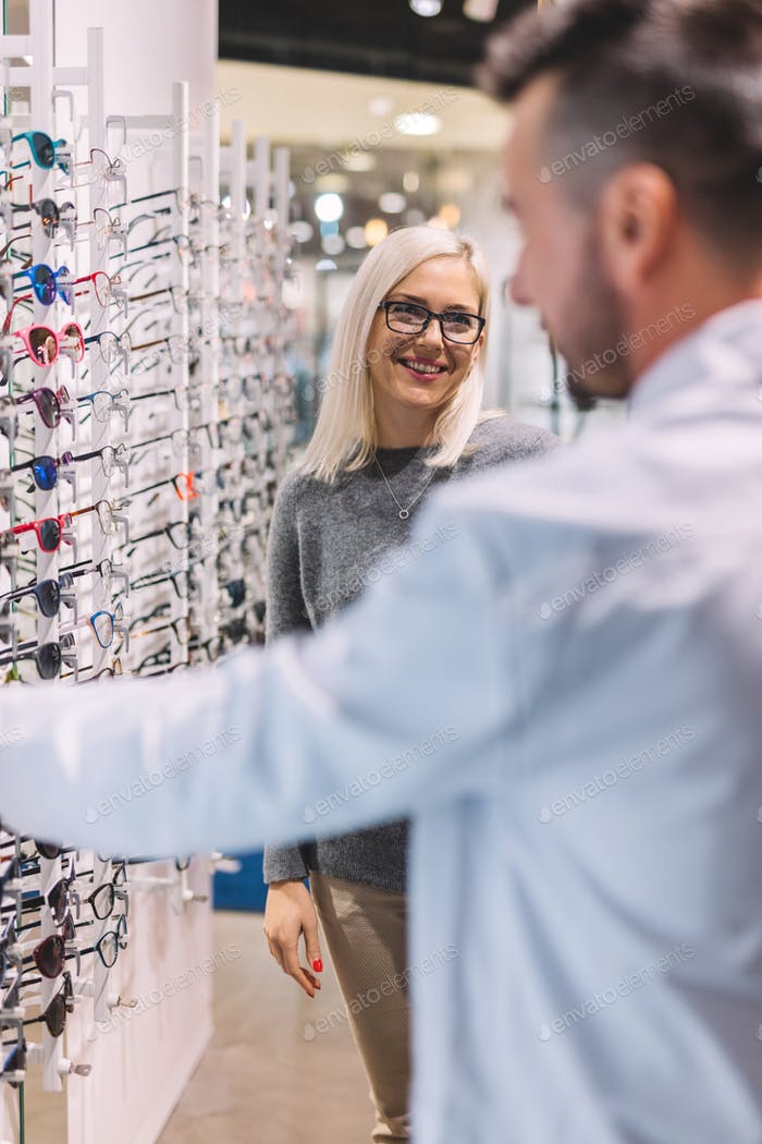 Woman and optician choosing glasses