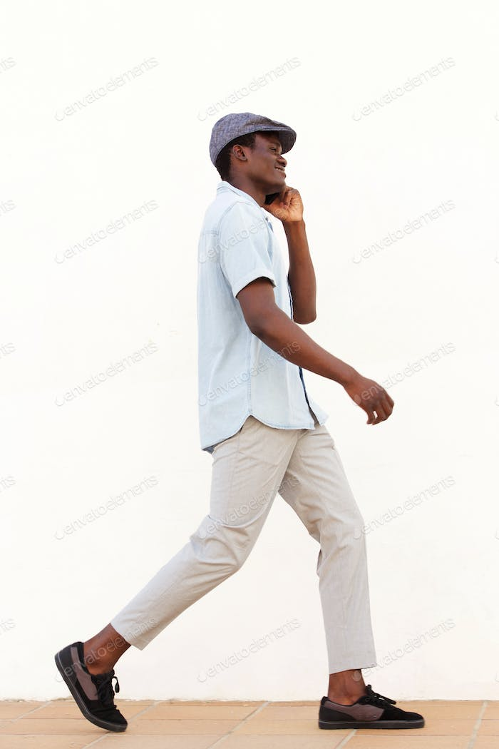Full body side of young african man walking outside talking on phone