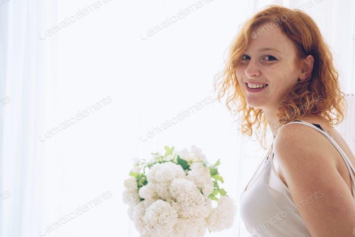 Portrait of redhead beautiful woman sitting near window at home