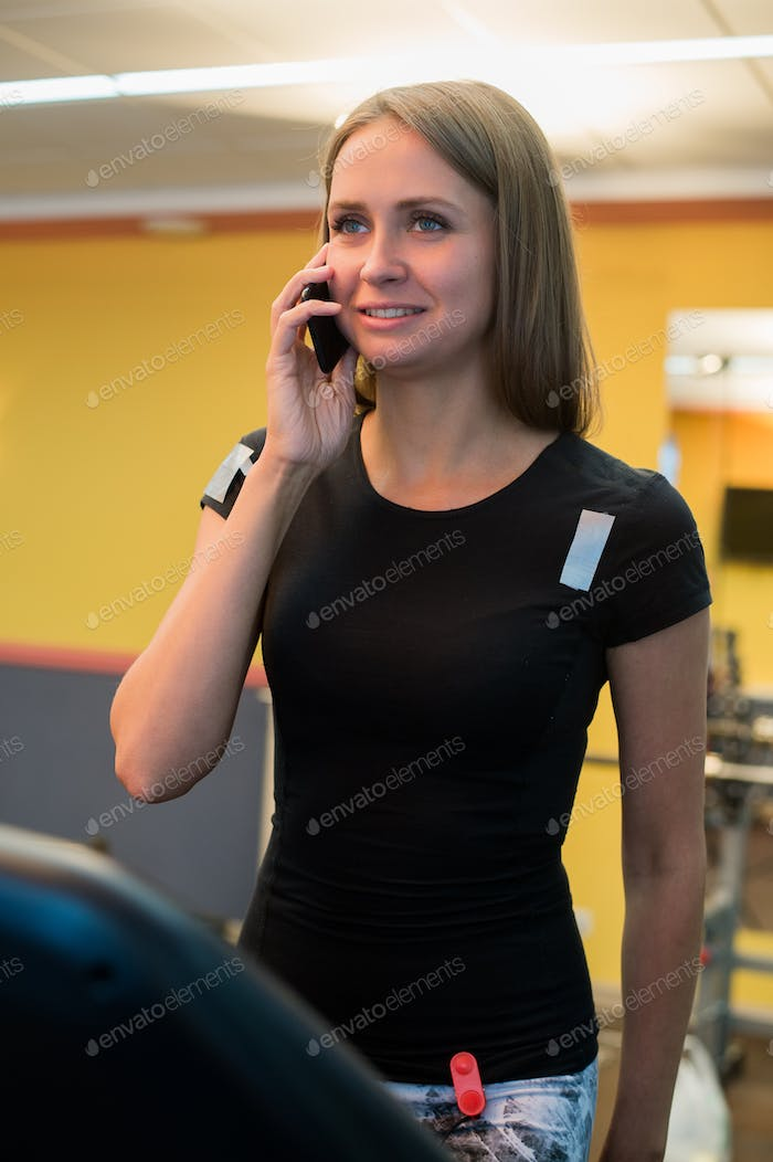 Sporty woman talking on mobile phone and holding water bottle in gym.