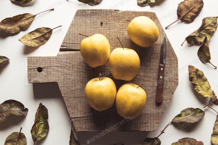 Gelbe Äpfel auf einem geschnittenen Brett im Vintage-Stil. Blätter, Lebensmittel, gesunde Lebensmittel, vegan, landwirtschaftliches Produkt