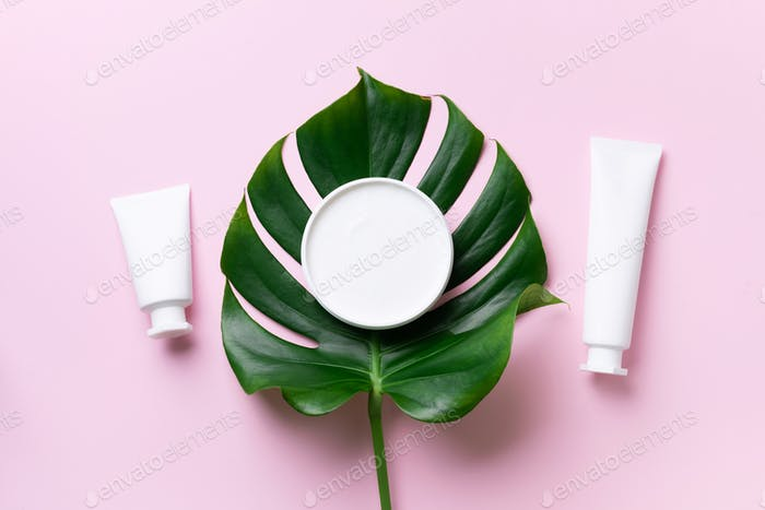 White plastic cosmetic jar, tube, bottle and tropical monstera leaf over pink background. Top view
