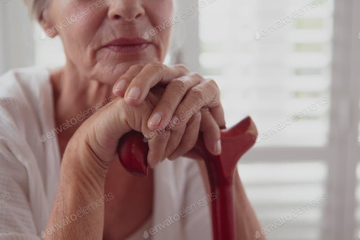 Mid section of active senior Caucasian woman leaning on walking cane in a comfortable home