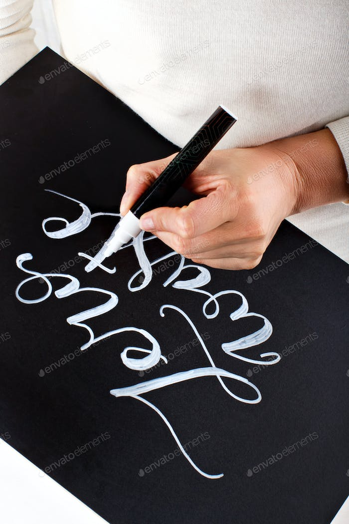 Woman writing on a small chalkboard zero waste lettering